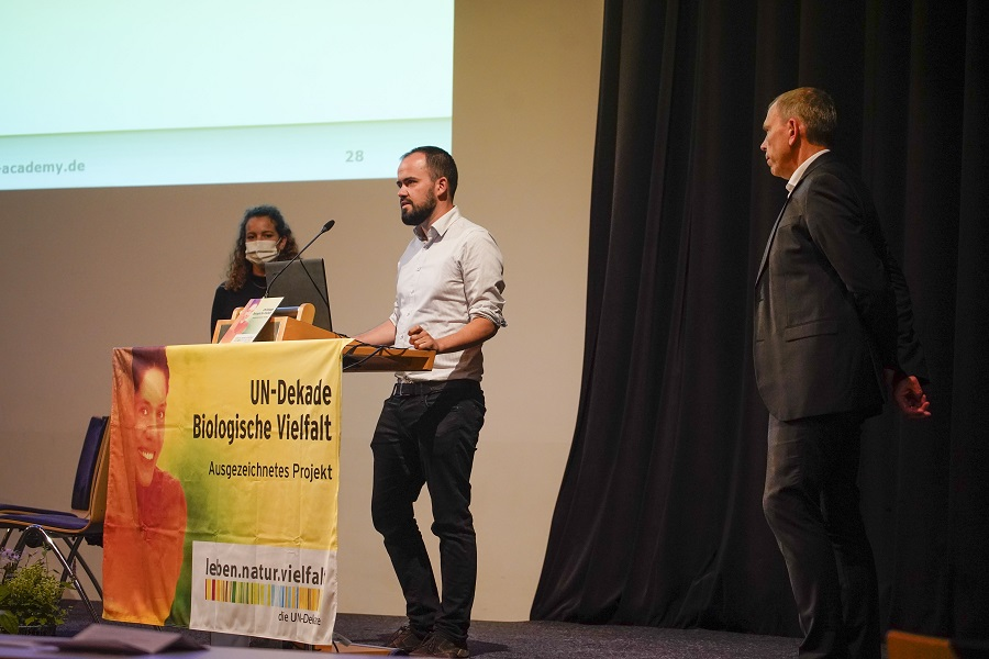 "Florian Fletschinger from FWTM accepted the 3rd prize on behalf of the trainees. - ""The jury particularly liked the fact that a new ""green"" area for break times was created here as a meeting point, which in turn has a positive effect on social interaction - a feel-good island with native plants was created."""